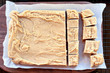 Whole block of delicious, homemade peanut butter fudge over a rustic wood cutting board being cut into squares.