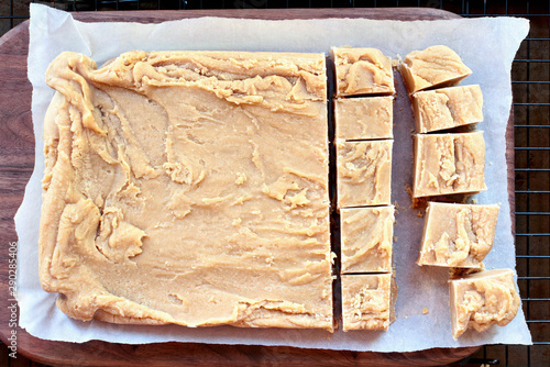 Photo Whole block of delicious, homemade peanut butter fudge over a rustic wood cutting board being cut into squares