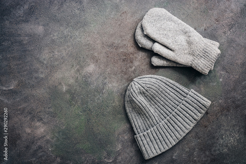 Fototapeta  Gray knitted hat and mittens on a dark rustic background