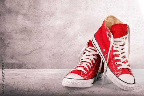 Pair of new red sneakers isolated on white background. Obraz na płótnie