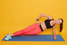 Close Up Portrait Of Young Sportive Strong Brunette Woman With Ponitail, Wearing Stylish Sportswear, Lady Doing Side Plank, Training At Home Or Gym. Fitness, Diet And Healthy Lifestyle Concept.