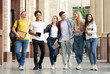canvas print picture - Multiracial students walking after classes in university campus