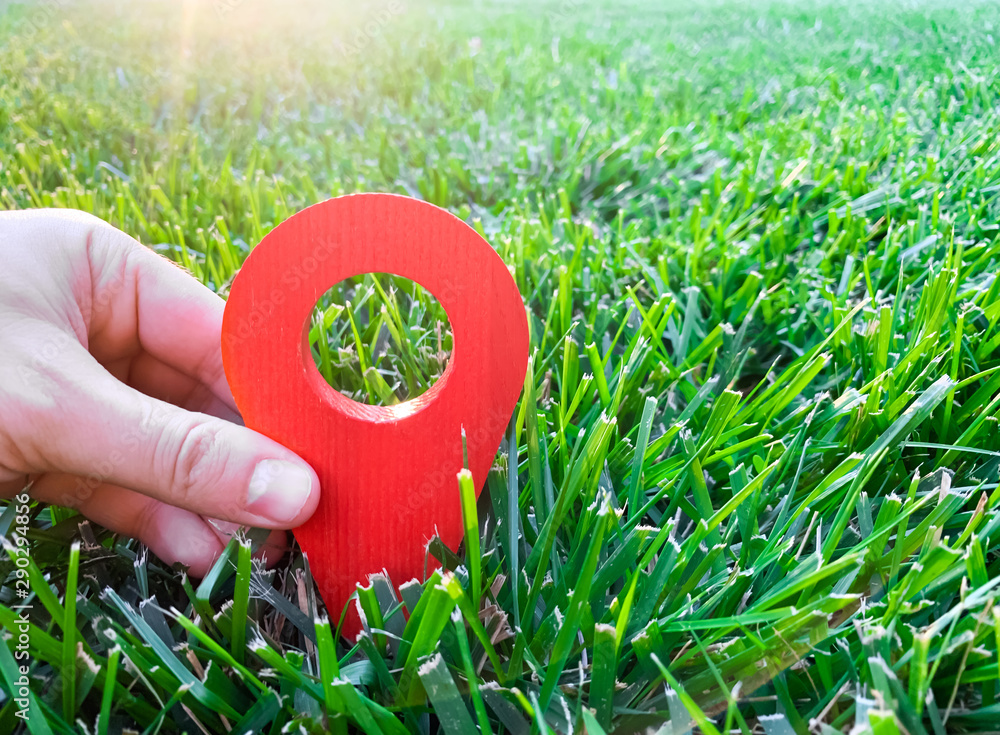 Fototapeta A hand is holding a red location marker in the green grass. The concept of tourism and travel. Navigation and exploration. Destination. Holiday, vacation. Buying building land. Selective focus