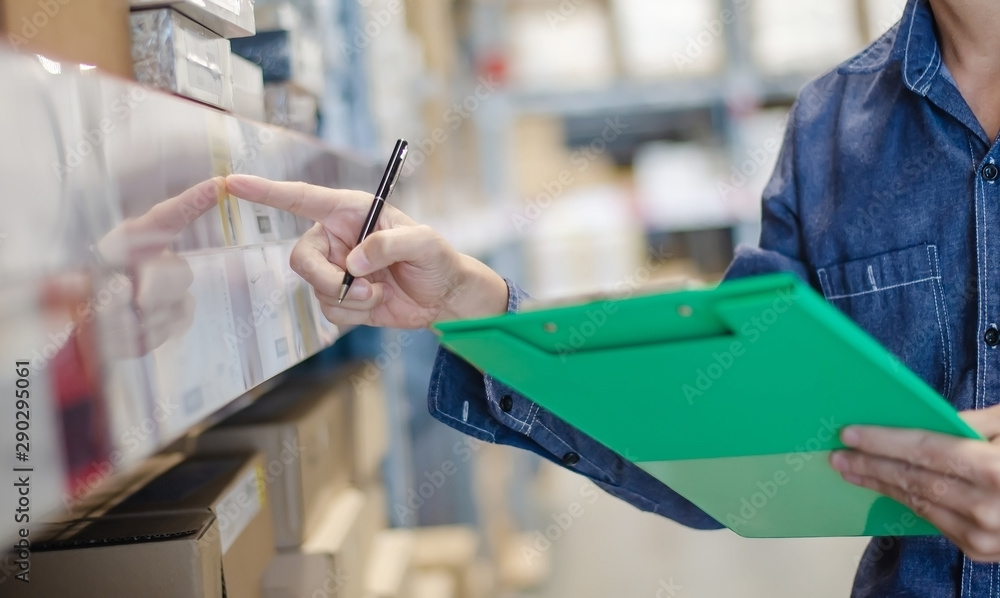 Fototapeta Asian manager man doing stocktaking of products management in cardboard box on shelves in warehouse using clipboard file and pen. Male professional assistant checking stock in factory.