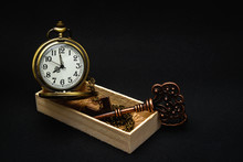 The Old Clock And Key That Were In A Wooden Box Placed On A Black Background.