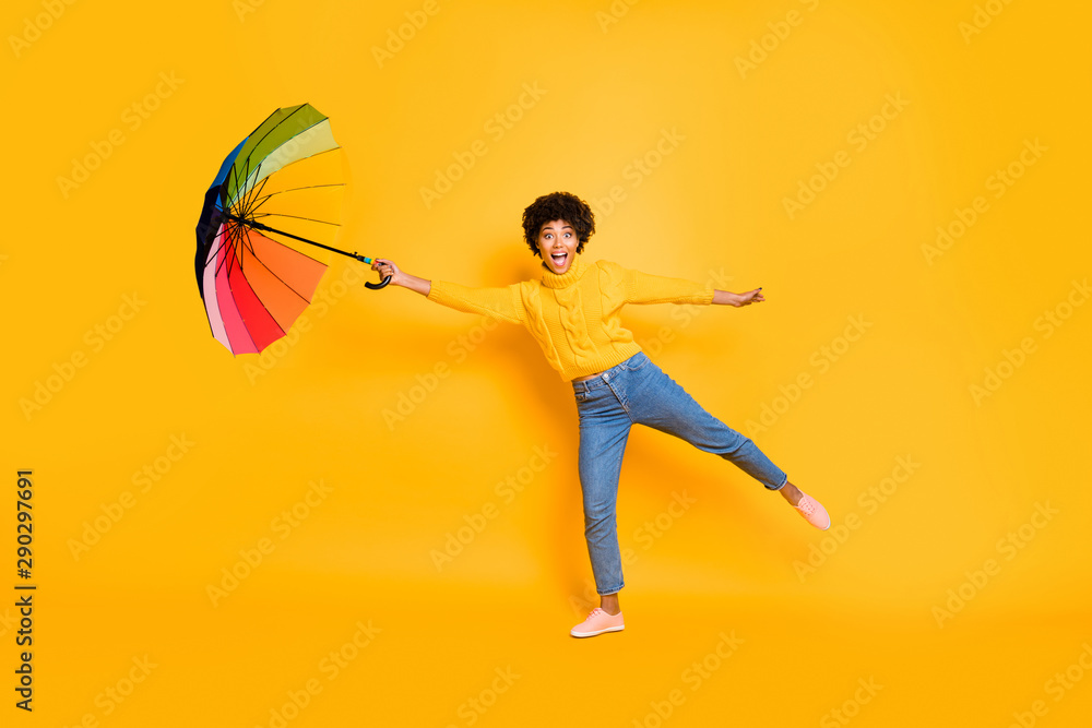 Fototapeta Hold on Adventures have just begun Full body photo of astonished excited cheerful shocked funky in jeans people trying to hold umbrella in hand and don't be blown away by wind isolated background