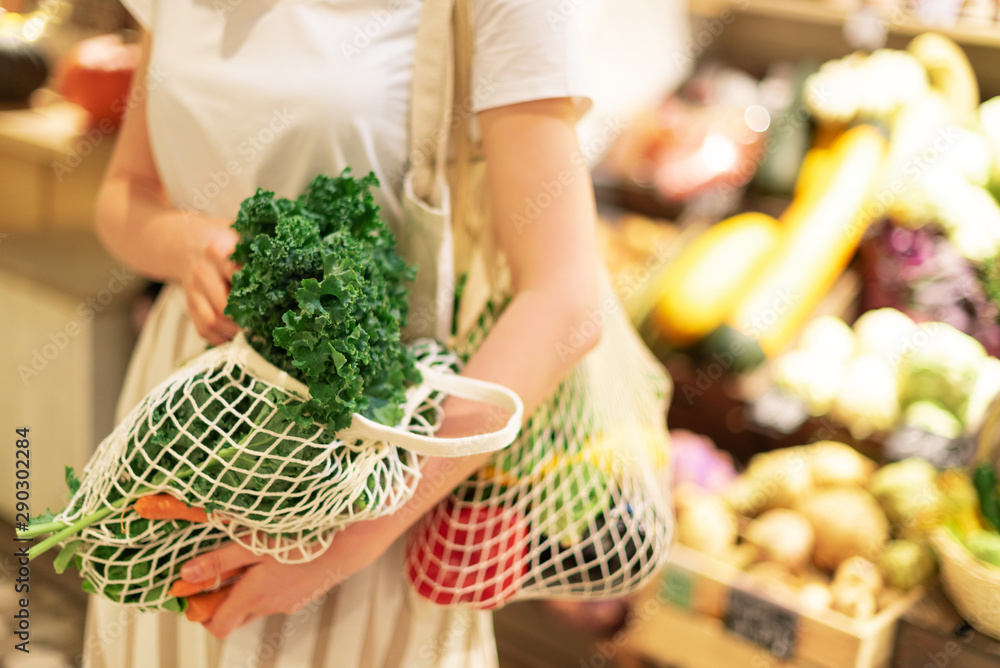 Fototapety, obrazy: Girl holding mesh shopping bag and cotton shopper with vegetables without plastic bags, wooden background. Zero waste, plastic free concept. Sustainable lifestyle. Banner.