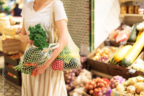 Obraz Zero waste concept with copy space. Woman holding cotton shopper and reusable mesh shopping bags with vegetables, products. Eco friendly mesh shopper. Zero waste, plastic free concept. - fototapety do salonu