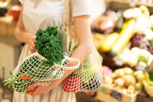 Girl holding mesh shopping bag and cotton shopper with vegetables without plastic bags, wooden background. Zero waste, plastic free concept. Sustainable lifestyle. Banner.