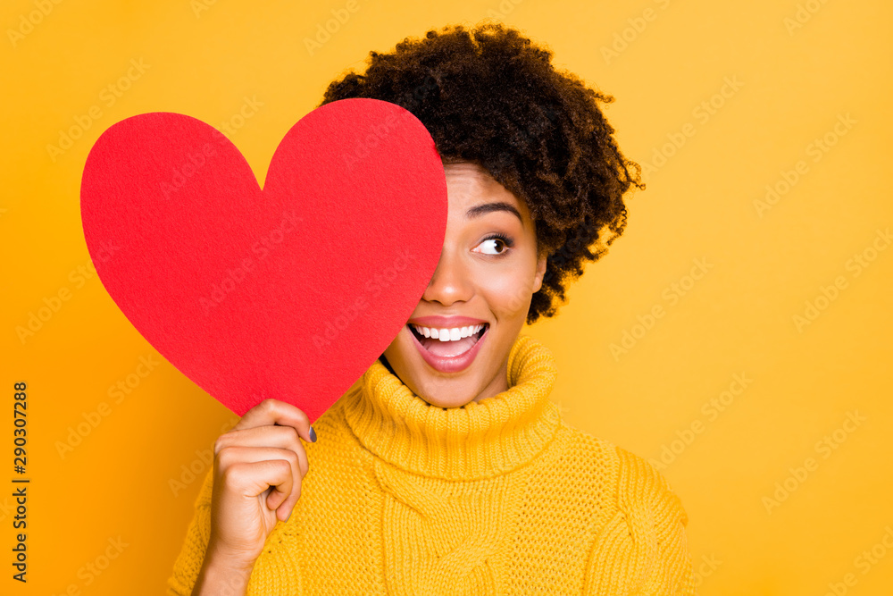 Fototapeta Photo of trendy cheerful cute nice charming curly fascinating girlfriend looking out away from red big heart wearing yellow jumper while isolated with bright color background