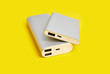 canvas print picture - Power bank for charging mobile devices. White smart phone charger with power bank. Battery bank on a yellow background . External battery for mobile devices.