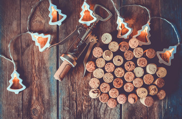 Wine corks, corkscrew and Christmas garland on a wooden table