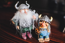 Two Gold Wedding Rings And Figurines On A Brown Table.Two Gold Rings On The Figure The Vikings..Two Viking Figurines