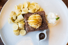 Close-up On, Honey Toast, Bread Buttered Toast, Banana, Ice Cream And Whipped Cream Dessert On A White Dish