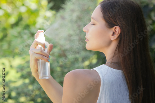 Woman spraying facial mist on her face, summertime skincare concept Fototapete