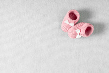 Baby Pink Shoes For Newborn Girl On Knitted Gray Plaid. Flat Lay, Top View, Copy Space