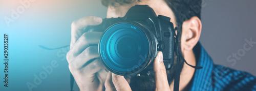 Obraz photographer hand camera on gray background - fototapety do salonu