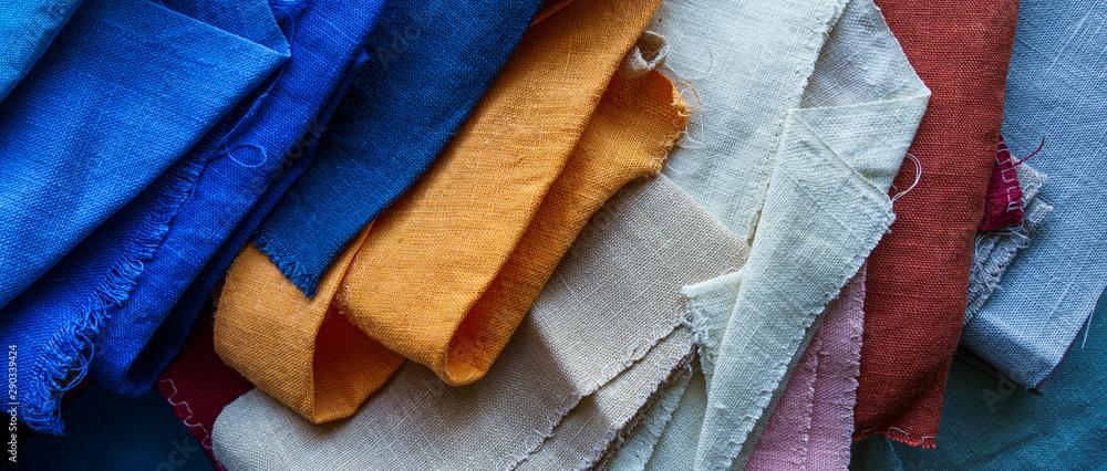 Fototapeta A stack of colorful fabrics background. Multicolored linen fabric