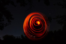 Spiral Drawn By Fire On A Dark Background. Red Spiral On A Black Night Background. Love, Romantic And Festival Concept