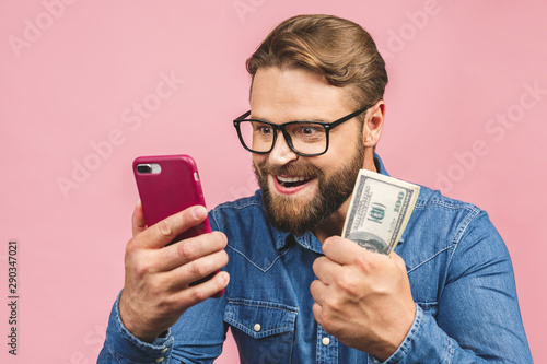 Happy winner! Bearded happy man demonstrating his money prize and using smartphone isolated over pink background Poster Mural XXL