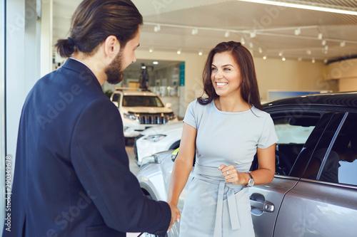 Girl buyer shakes hands dealer a car