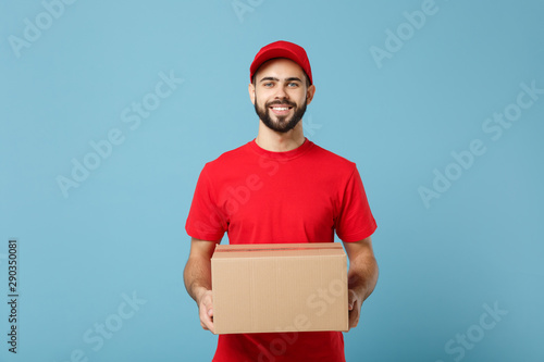 Foto  Delivery man in red uniform isolated on blue background, studio portrait