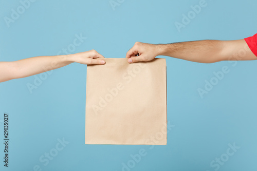 Obraz na plátně Close up cropped hands hold brown clear empty blank craft paper bag box food for takeaway isolated on blue background