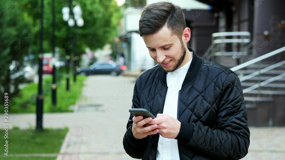 Fototapeta Handsome young bearded man uses the phone on the street in, typing text, chatting with friends