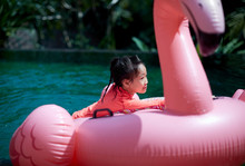 Cute Asian Little Girl Swimming In Outdoor Infinity Pool And Holding Colored Life Buoy.closeup