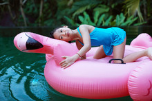 Cute Asian Girl Playing In The Pool With Flamingo Water Toy. Shot By 120 Films