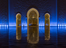 A Man In Traditional Dress Walks By The Entrance Of The Sheikh Zayed Grand Mosque, Abu Dhabi, UAE At Night