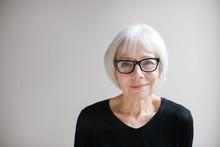 Studio Portrait Of Senior Woman On Simple Grey Background