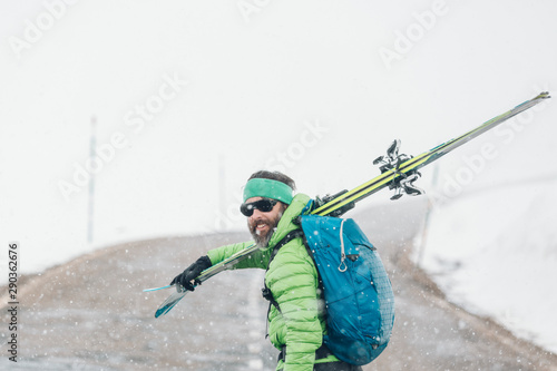 Skier walking along empty road in the snowy mountains in winter carrying skis
