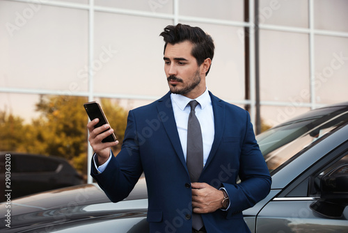 Attractive young man with smartphone near luxury car outdoors