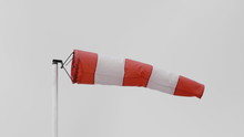 Frayed Windsock In Moderate Wind Against Blue Sky