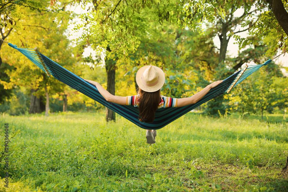 Fototapeta Young woman resting in comfortable hammock at green garden