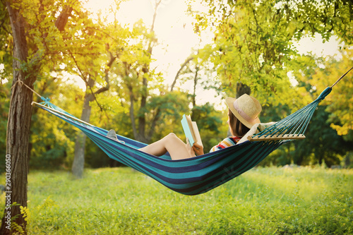 Young woman reading book in comfortable hammock at green garden Canvas
