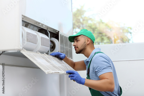 Cuadros en Lienzo  Professional technician maintaining modern air conditioner indoors