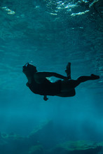 A Young Women Swimming Beneath The Surface Of Clear Blue Water In A Cenote In Mexico.