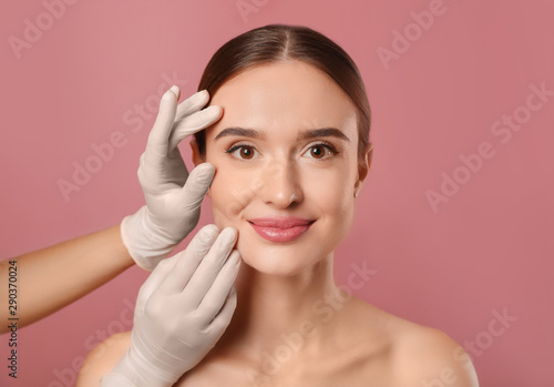Valokuvatapetti Doctor examining woman's face before plastic surgery on pink background