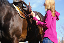 Woman Putting Saddle On Horse Close Up For Western Horseback Riding Concept.