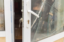 A Broken Glass Window In An Aluminum Frame Door. Door Is Padlocked