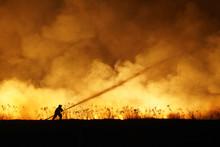 Silhouette Of Fireman Fighting...