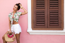 Beautiful And Stylish Woman Posing Beside The House With A Pink Wall