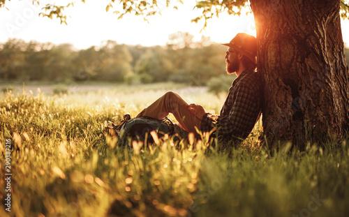 Obraz Bearded traveler resting near tree - fototapety do salonu