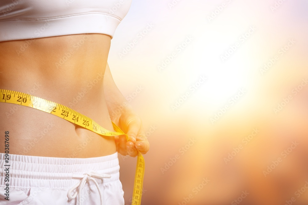 Fototapety, obrazy: Slim young woman measuring her thin waist with a tape measure, close up