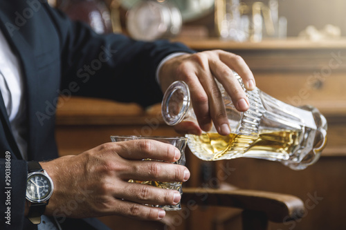 Man pouring whiskey into the crystal drinking glass Wallpaper Mural