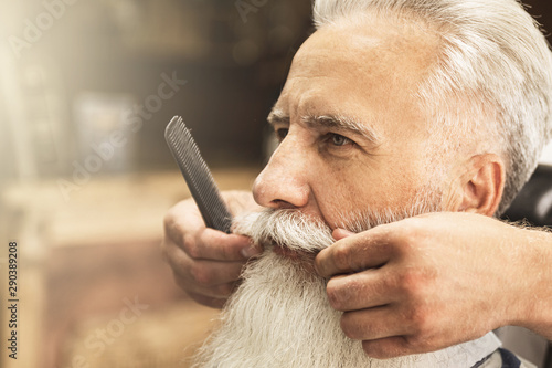 Handsome senior man getting styling and trimming of his beard Canvas Print