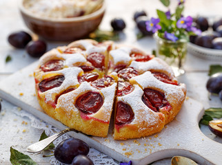 Plum cake, traditional homemade cake with fruit, divided into portions, sprinkled with powdered sugar on a white board, close-up view. Fruit cake, dessert