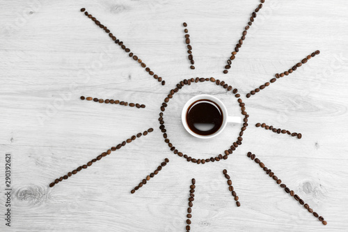 Coffee grains folded in the form of the sun on a wooden background. In the middle is a cup of coffee, meaning it's time to drink coffee after sunrise